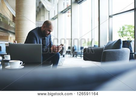 Man professional banker is reading text message on mobile phone while is resting after work on laptop computer. Male entrepreneur is using cellphone while is waiting business lunch in restaurant