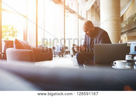 Young successful businessman is reading e-mail in internet on mobile phone while is resting after webinar conference via net-book. Male manager is searching information on web site via cell telephone