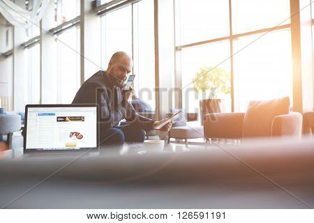 Angry businessman is holding touch pad in hands and communicating via mobile phone with the bank's support who locked his credit card while is sitting near open net-book with web page on screen