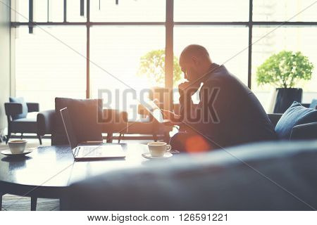 Serious man banker is examining future banking agreement via digital tablet while is sitting in an informal setting. Male leadership is reading on touch pad important documents received on e-mail