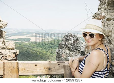 Young caucasian woman in a sailor outfit is posing on the ruins of the castle Cachtice. Travelling theme.