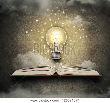 the concept of enlightened ideas, an open book with a light on a dark background