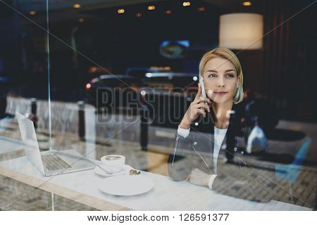 Beautiful hipster girl is phoning via smart phone while is sitting at cafe table with laptop computer. Female student is calling via cell phone while is resting after on-line learning via net-book