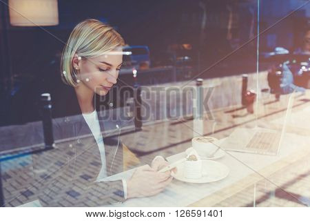 View through window of a young female student is playing games on mobile phone while is resting after learning on portable laptop computer while is sitting in cafe before her lectures in university