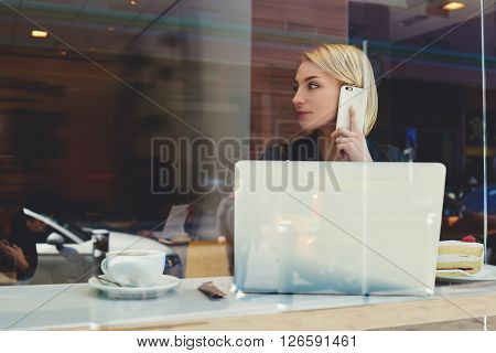 View through window of a young businesswoman is calling via mobile phone to her partner which she waiting in coffee shop. Hipster girl is phoning via cell phone during work on portable laptop computer
