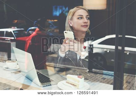 View through window of a charming hipster girl with cell phone in hands is thinking what to write in text message for her boyfriend while is sitting in modern cafe-bar with portable laptop computer