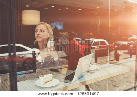 View through coffee house window with city reflection of woman is using mobile phone while is waiting file download on net-book. Young female with smart phone is resting after work on laptop computer