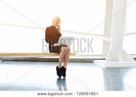 Woman designer of websites is talking on mobile phone with customer while is sitting with laptop computer in co-working space. Pretty female with net-book on knees having cell telephone conversation