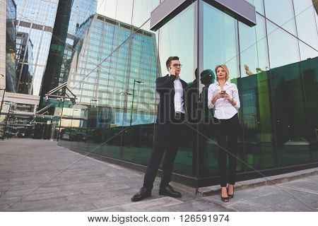 Young man boss in suit is having cell telephone conversation while is standing with female partner outdoors. Blonde woman is holing cellphone in hands while her boss is talking via mobile phone