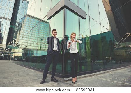Man intelligent economist is phoning via cell telephone while is standing with partner outside the company where they work. Blonde female is checking time while her boss is talking on mobile phone