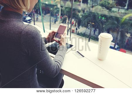 Closely of woman is typing text message on cell telephone while is resting in coffe shop of modern shopping center in Hong Kong. Young hipster girl is chatting in social network via mobile phone