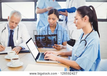 Female doctor using laptop in conference room and colleagues examining a x-ray in background