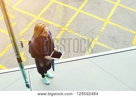 Top view of hipster girl dressed in stylish clothes is holding touch pad with copy space on the screen. Young cheerful woman with digital tablet in hands is smiling for someone. Unusual perspective