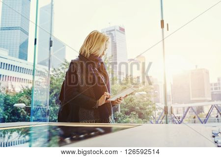 Woman tourist is searching in internet via touch pad a place where she could dine during travel in China. Female is chatting in social network via digital tablet while is standing in business center