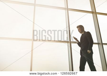 Stylish business man in the background of a large window in the floor. The model uses a mobile phone.