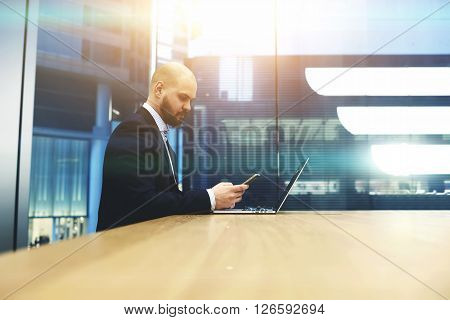 Bearded businessman is calculating the income of the firm last month by using cell telephone and portable net-book. Young male proud banker checking with mobile phone the state of the currency market