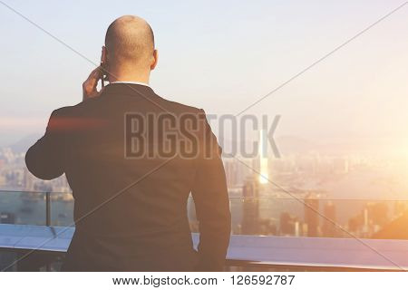 Back view of man is talking on mobile phonewhile is standing on a skyscraper roof against Honk Kong city. Skilled male CEO is having serious cell telephone conversation during business trip in China