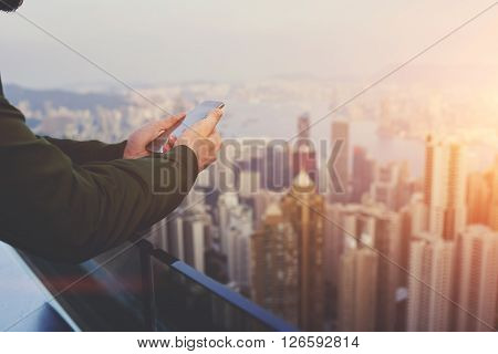 Closely of man successful broker is using mobile phonewhile is standing on building roof against view of Hong Kong city with tall skyscrapers. Hipster guy is connecting to internet via cell telephone