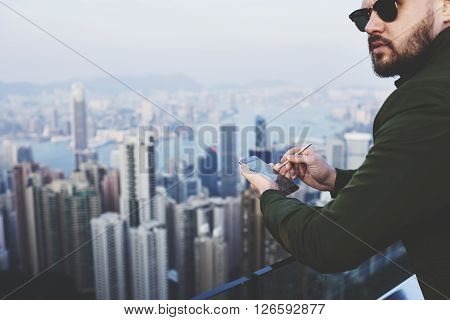Closely image of a bearded hipster guy in fashionable sunglasses with mobile phone in hand is looking away while is standing on building roof against blurred business district skyscrapers in New York