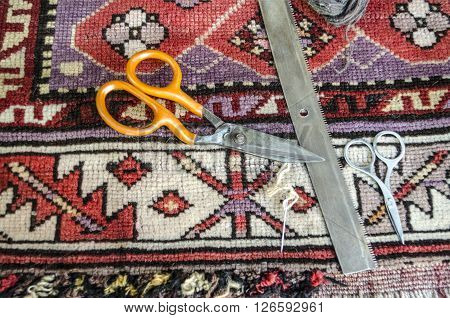 Comb,scissors,needle and woolen thread for the restoration of the old of worn woolen carpet