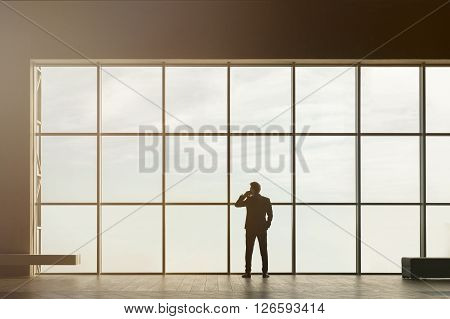 Stylish business man in the background of a large window in the floor. Model talking on the phone.
