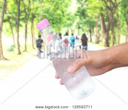 Hand holding plastic water bottle over blur background of people cycling in the park