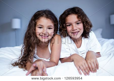 Portrait of brother and sister lying on bed in bedroom