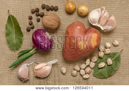 Raw potatoes, onions, chickpeas and spices, lying on an old wooden surface