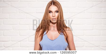 sexy woman with brown hair and blue top on the brick wall
