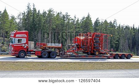PAIMIO FINLAND - APRIL 15 2016: Scania R620 Semi truck hauls Vaderstad Spirit 800C seed drill along motorway in high speed.