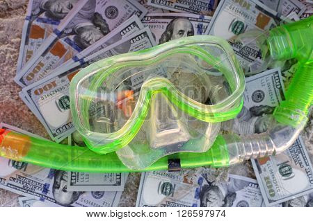 US dollars and some diving equipment spread out over sand concept of vacation expenses
