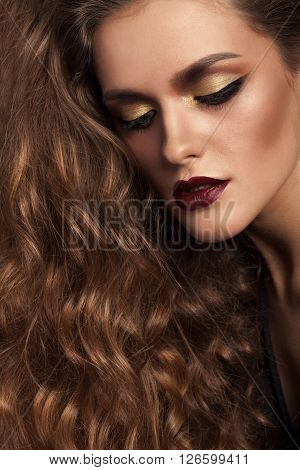 Woman with rich hair and gorgeous hairstyle and gold make up in studio. Hair and hairstyle. Salon make up and hairstyle. Advertising use