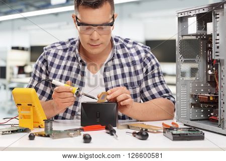 Young PC technician working with soldering iron on a computer chip in a workshop