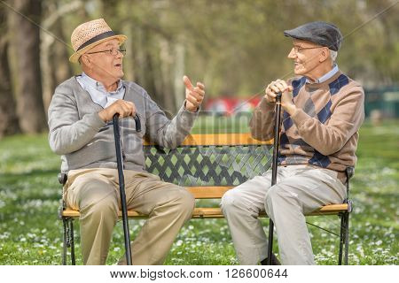 Two cheerful senior gentlemen talking to each other seated on a bench in a park