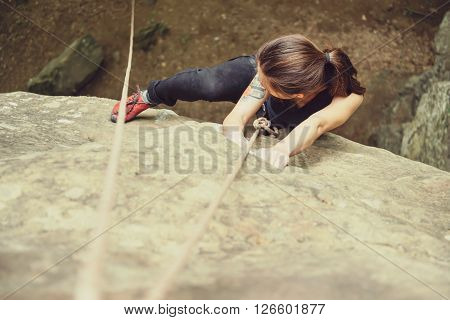 Sporty young woman wearing in safety equipment with rope climbing on rock mountain in summer outdoor top view
