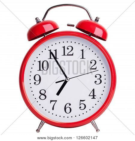 Round red alarm clock shows five to seven