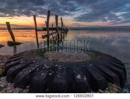 big old tyre with broken wooden bridge after sunset