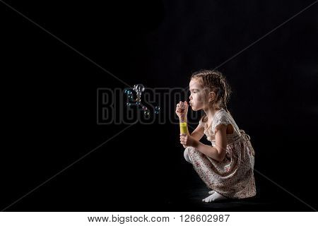 cute beautiful little girl and soap bubbles . happy child. girl blows soap bubbles on a black background