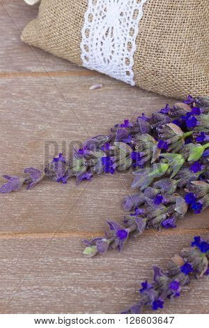 Lavender fresh flowers and dry ones in pouch on gray wooden table