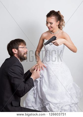 Beautiful bride with fashion wedding hairstyle. Close-up portrait of young gorgeous bride. Bride pointing a gun at the bridegroom, while he wears the ring on her finger.