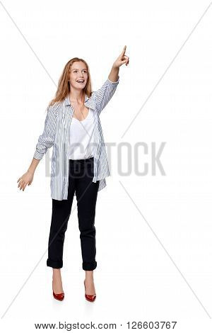 Happy excited woman in full length pointing to the side at blank copy space, over white background