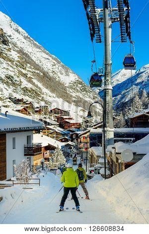 ZERMATT SWITZERLAND - FEBRUARY 05 2016: People skiing in the streets of Zermatt in Switzerland.
