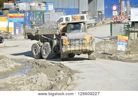Dolny Hricov Slovakia - April 13 2016: Dirty heavy Volvo dumper loaded by rock moving in work site. There is slovak highway labeled