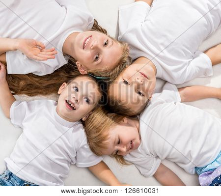 smiling children lying with their heads together isolated on white background