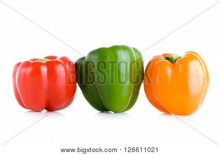 Red, green and orange peppers lined up on a white background