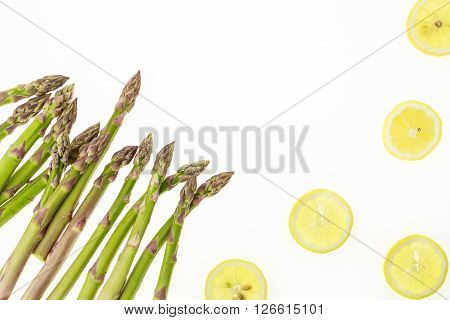 Bunch Of Asparagus Spears And Lemon Slices, On White Background With Copy-space