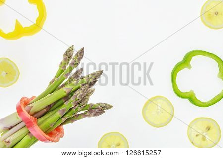 Bunch Of Asparagus Spears With Lemon Slices And Bell Pepper Rings, On White Background With Copy-spa