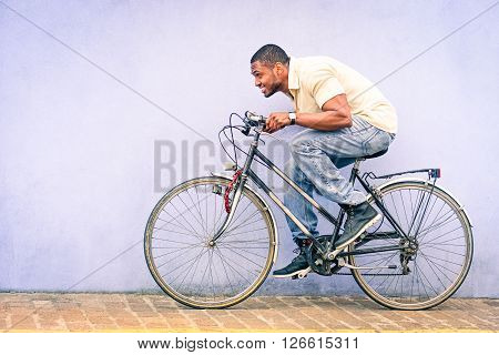 Black American African man in funny scene with locked old bike - Young afroamerican guy riding vintage bicycle with red padlock safe chained to wheel - Fun concept of cycle theft and security tools