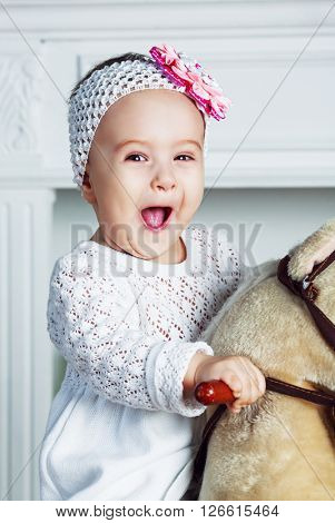 happy baby playing at home with a toy horse