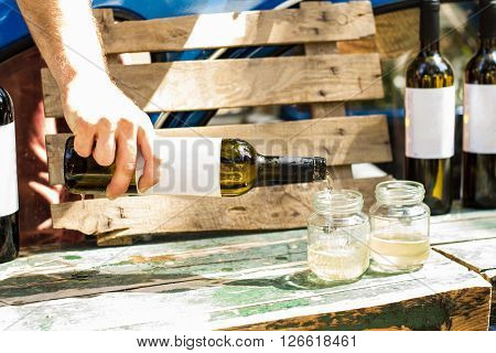 Pour white wine from the bottle into glass jars